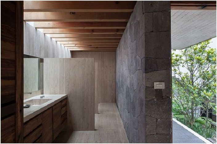 Unusual bathroom with an interesting interior that highlights the hidden lighting and a stone wall.