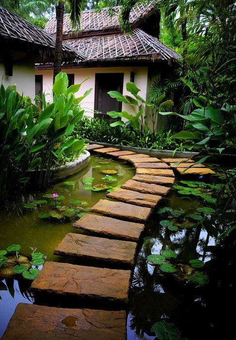 Красива каменна пътека в средата на огромно езеро в градината.