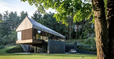 Playing on contrasts: modern villa, partially integrated into the green hill