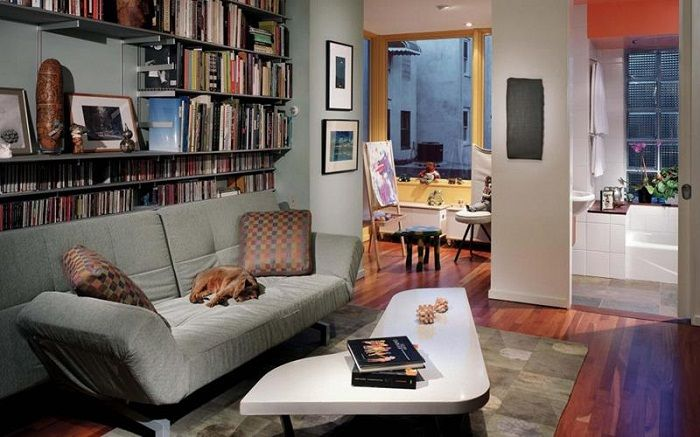 Small irregularly shaped table and bookshelves create artistic interiors in the tiny living room.