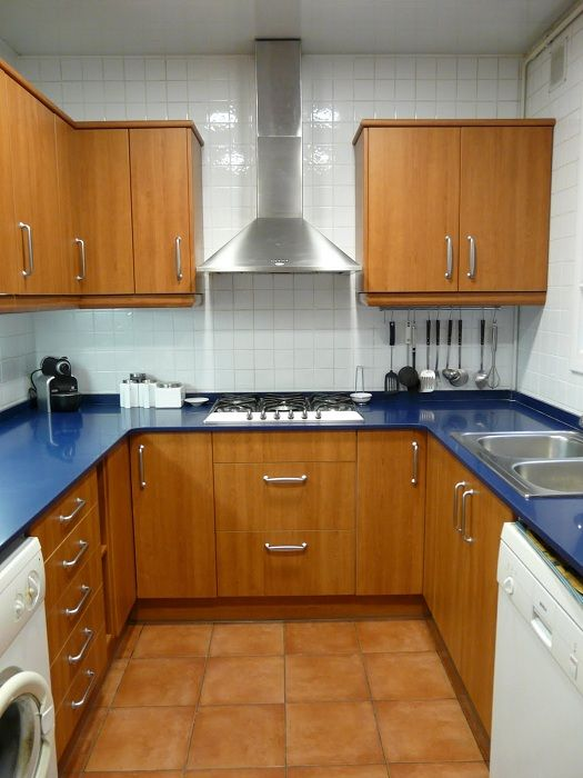 The kitchen is located in a small square framed in wood with excellent blue tops.