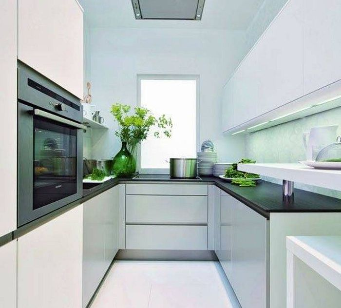 A great example of design of a kitchen with a small area in light colors with dark tops.