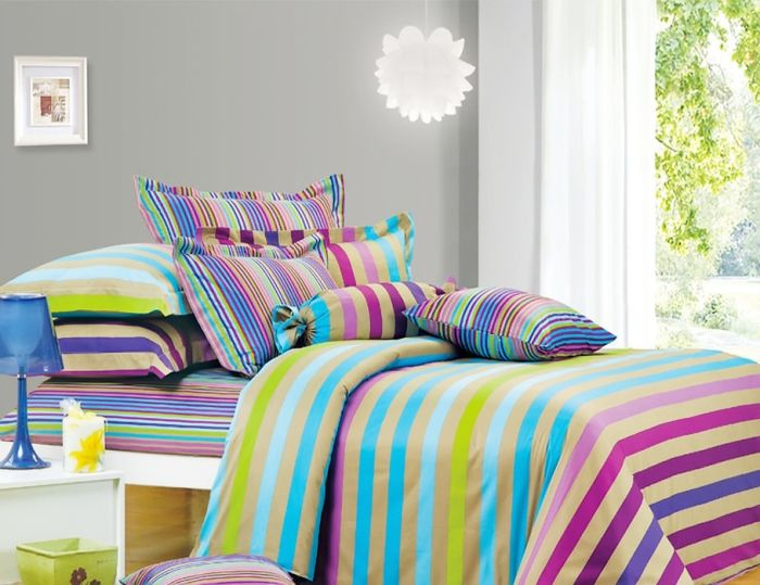 Bright bed linens enliven the interior of the bedroom.