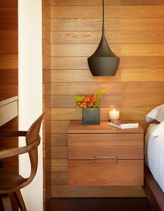 An interesting option to decorate the bedside space with a wooden niche with two drawers.