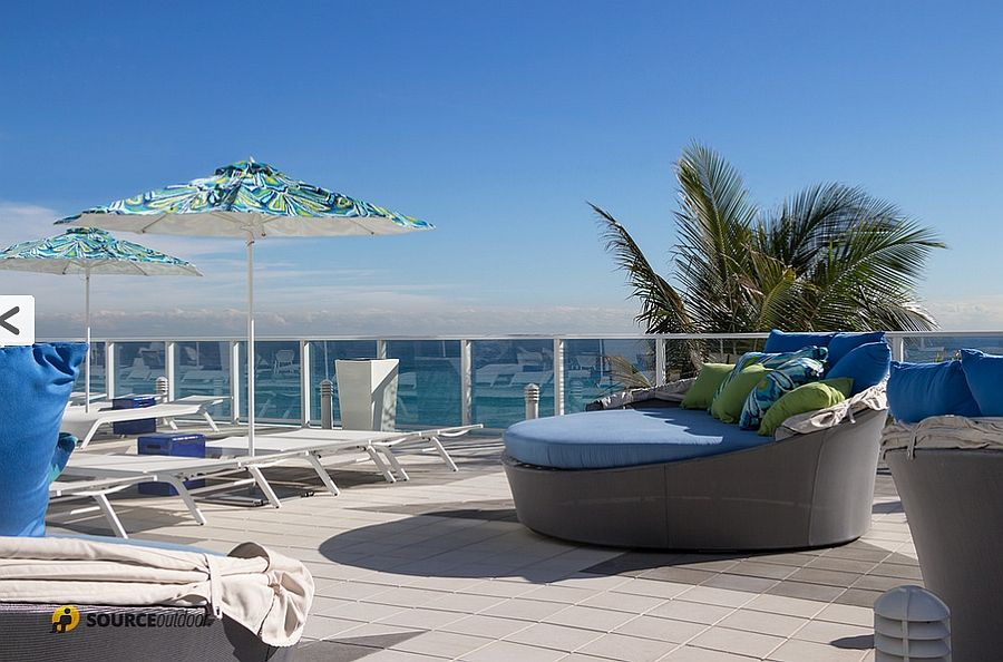 Chic aqua couches, lounge chairs and sun umbrellas on the terrace