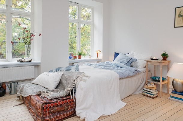 interior-bedroom-swedish-apartment-white-room-glass-window-small-apartment-interior-design-flower-vase-wooden-floor-bedside-table-bedside-lamps-blue-white-navy-pillow-aztec-suitcase-white-bedco
