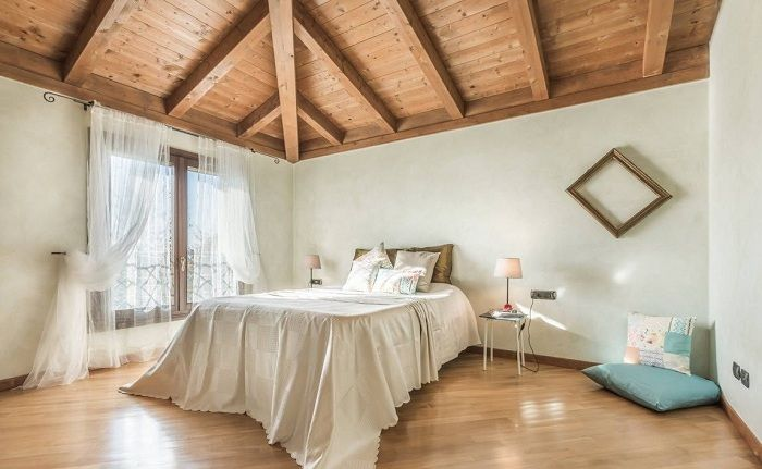 The original decor of the room for sleeping with a wooden ceiling and a lovely white curtains.