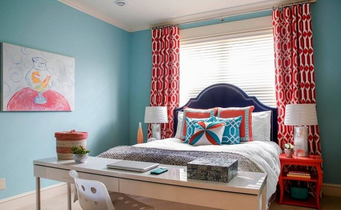 Interesting design of bedroom with blue walls and original scarlet curtains.