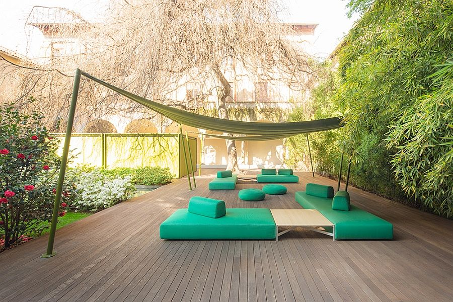 Green sofa, ottomans, sofas and wooden table on the terrace