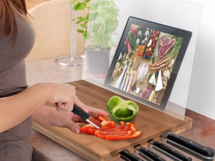 A convenient example of a successful arrangement of the workplace in the kitchen - the board with a stand for the tablet.