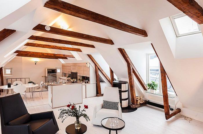 The successful placement of the kitchen to the living room passing under the loft, which adds a certain charm to the interior.